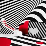Le sneakers hi-top Rebel e l'iconica pochette con cerniera per un'insolita visione dell'amore, molto chic, firmata Hogan. La limited edition della maison per San Valentino si tinge di bianco e nero a righe optical, per lasciarsi ipnotizzare dall'amore ed è rifinita da un cuore applicato a stencil.