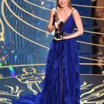 """Brie Larson, premio Oscar come Miglior Attrice per la sua interpretazione in """"Room"""", ha indossato un abito realizzato appositamente per lei, in organza di seta blu, con gonna plissè e dettagli di ruches a cascata, impreziosito da una cintura gioiello in velluto nero interamente ricamata con cristalli, perle e fiore in seta viola. A completare il look, sandali a tacco alto con plateau aperti in punta in raso blu di Gucci."""