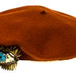Basco in lana cotta color ocra rossa impreziosito da una spilla con occhio di perle e strass, di Rada'