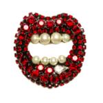 Spilla a forma di bocca ricoperta di strass rossi e dai denti ricoperti di perle di Radà.