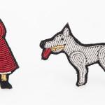 M Collective: spilla in tessuto raffigurante cappuccetto rosso di Macon&Lesquoy.
